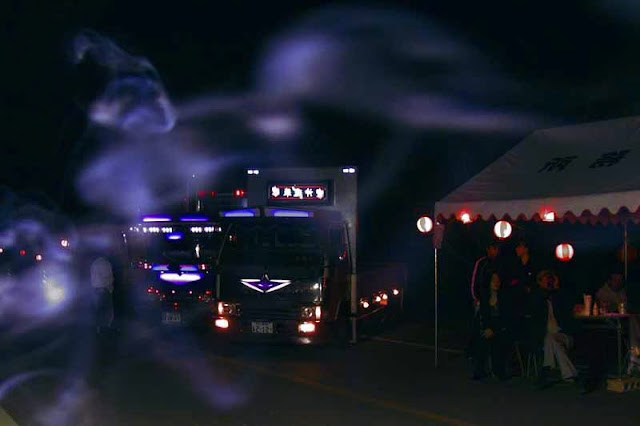 night scene, trucks and smoke, a ghost-like imagery