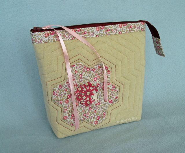 Make a zippered bag with Liberty, hexagons, flowers and echo quilting. Use it as a makeup bag, toiletry bag - lots of uses ~ Threading My Way