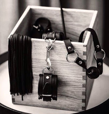 wooden box with BDSM toys: whip, ball gag, cuffs, riding crop