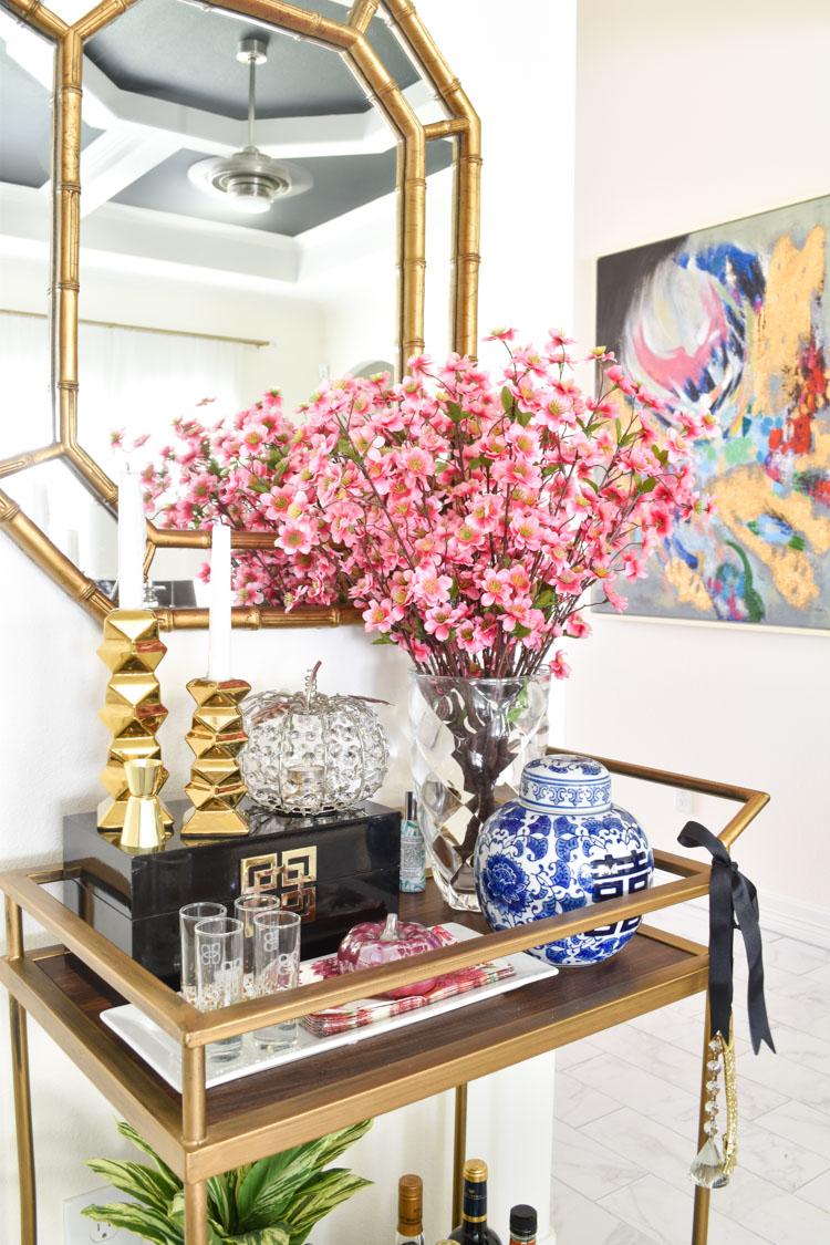 Vintage gold gilt bamboo mirror over a bar cart with fall and chinoiserie decor. #barcart #goldbarcart #entertaining
