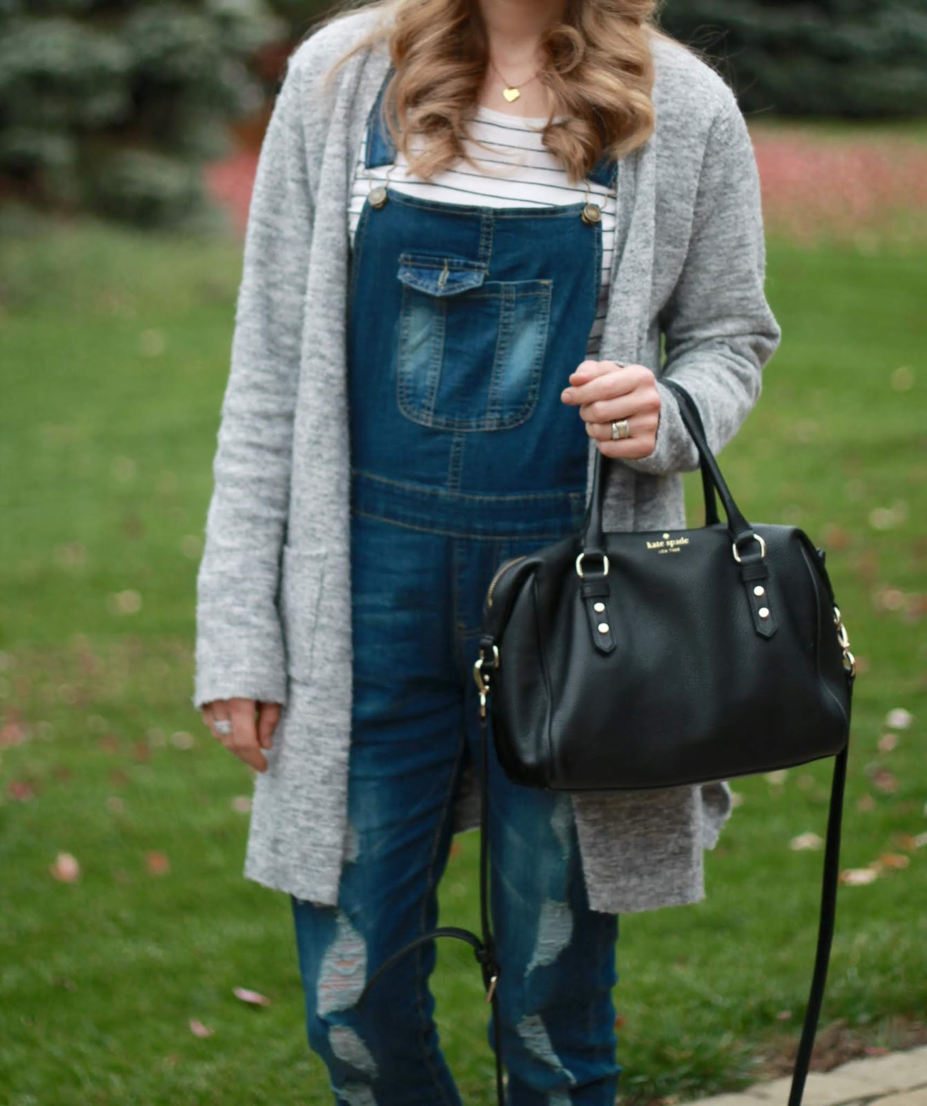 striped tee, distressed overalls, great boyfriend cardigan, white fur pom pom beanie, white and gold tennis shoes, black kate spade crossbody