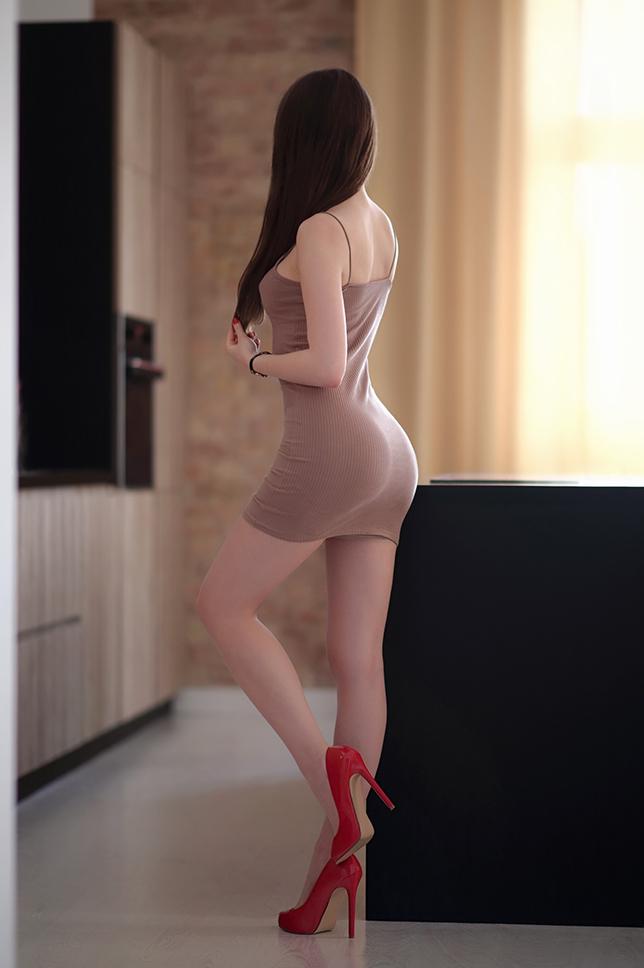 Beżowa obcisła sukienka, cieliste pończochy i czerwone szpilki