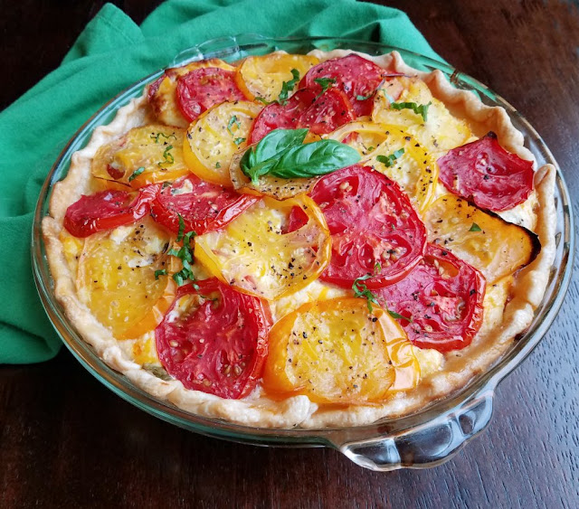 cheesy tomato pie with yellow and red tomatoes and basil