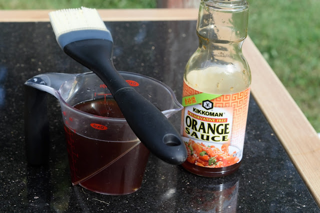 A measuring cup, basting brush, and bottle of orange sauce.