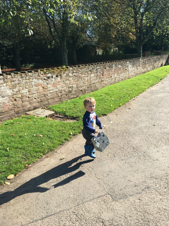 Birthday-boy-toddler-in-sunshine-holding-a-bag