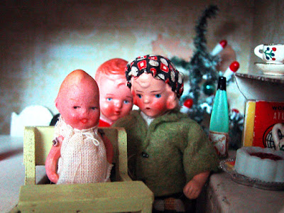 Three vintage dolls-house dolls pose for a picture in front of a Christmas tree and a sideboard set up for Christmas