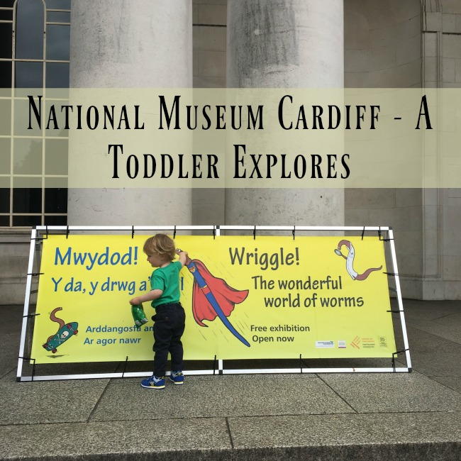 National-Museum-Cardiff-a-toddler-explores-text-on-picture-toddler-next-to-sign-outside-museum