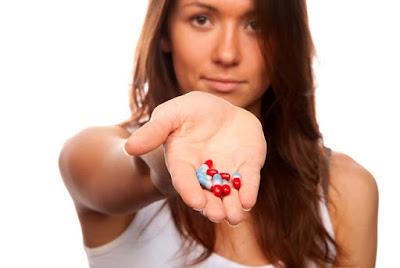 mujer con capsulas en la mano