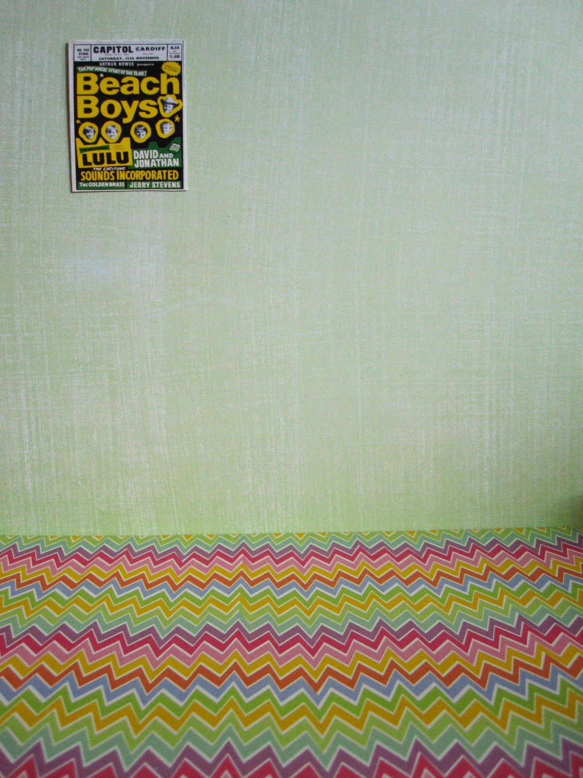 Bright 1960s Beach Boys poster on a green wall with a bright zig zag-patterned floor.