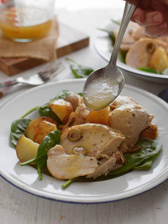Pollo con papas al horno servido sobre una cama de espinacas y bañado en una salsa o vinagreta de limón