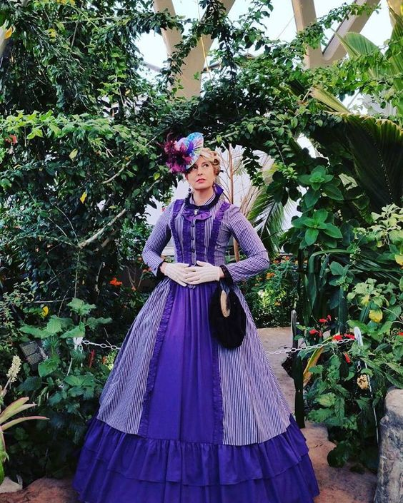 Woman wearing a purple striped Victorian gown (bodice + skirt) with white lace gloves and Victorian hat. Women's Victorian costumes and clothing