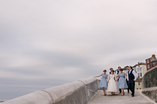The bridal party walk to the beach