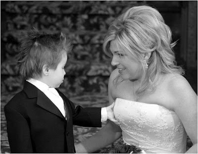 Little boy tweaking bride's breast