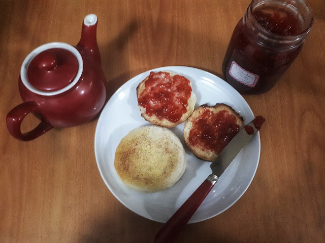 Homemade English muffins and jam on a plate with a knife and a teapot beside the plate