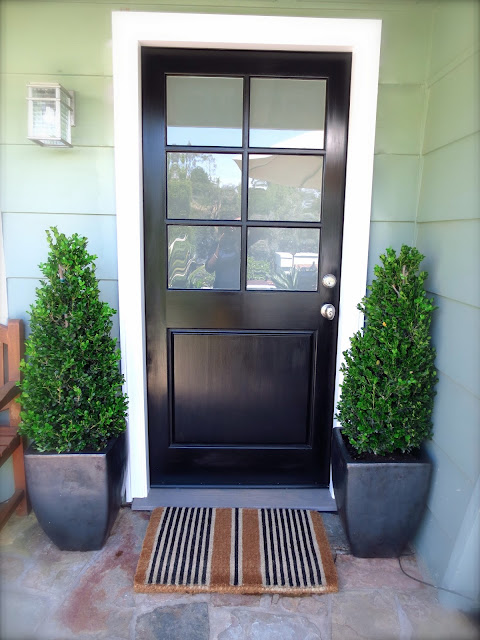 black front door frosted glass stripe striped doormat mat boxwood topiary plants decor design