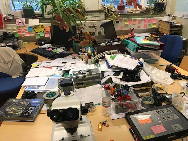 Hyvin täysi toimisto, jossa ei tyhjää pöytätilaa löydy, ja muistilappuja on joka paikassa.
