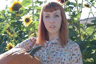 daughter holding pumpkin in my garden sunflowers