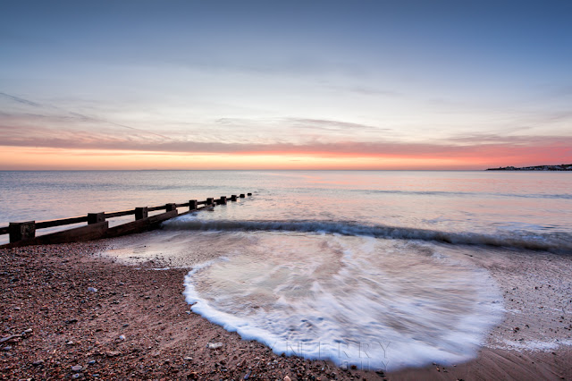Waves spread over the beach at Swanage in the dawn light
