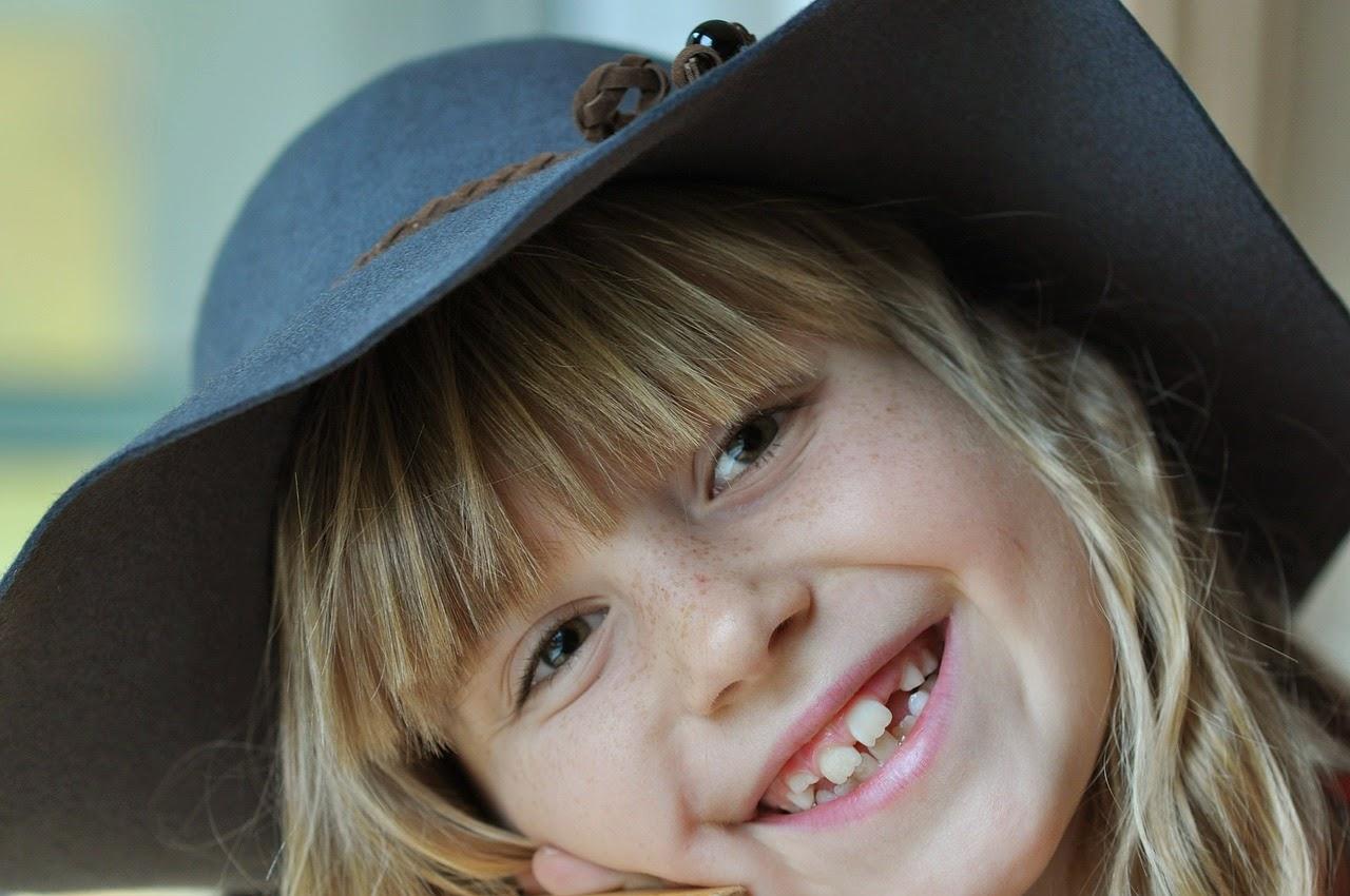 Kind lacht mit bleibenden Zähnen