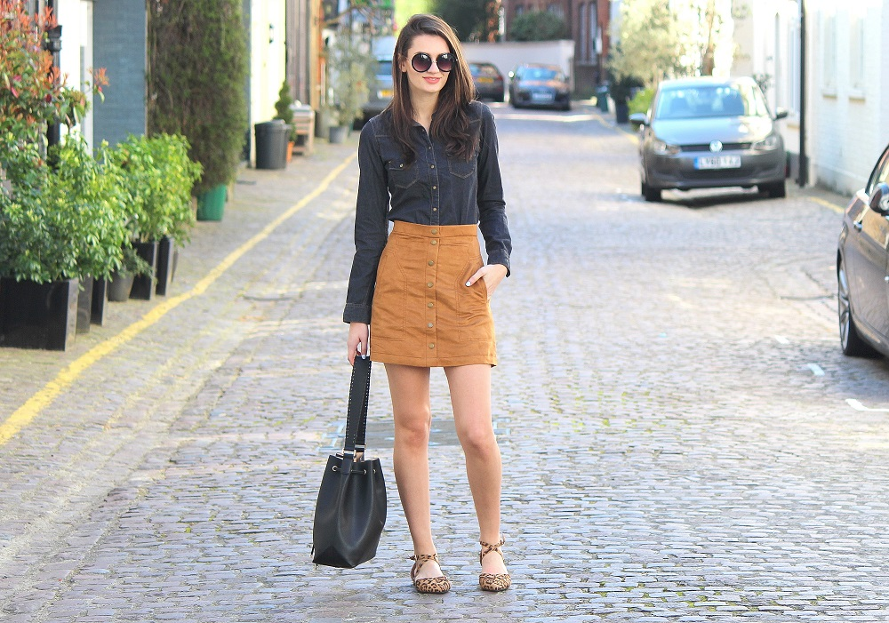 peexo fashion blogger wearing denim shirt and suede skirt and bucket bag and leopard print shoes
