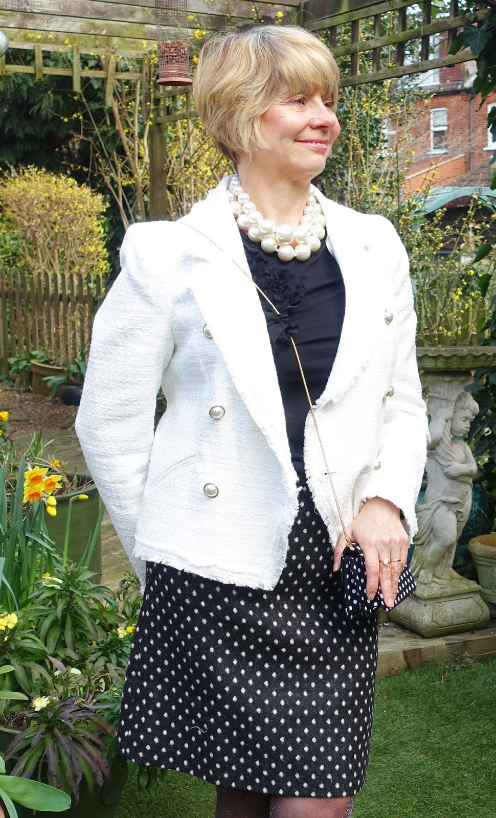 Image showing a woman in a spring garden wearing a white bouclé jjacket with polka dot skirt, shoes and bag