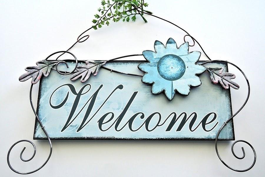 placa de bem vindo com armação de metal e flores