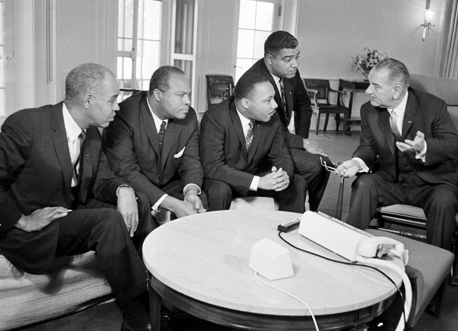 In this January 18, 1964 photo, U.S. President Lyndon B. Johnson, right, talks with civil rights leaders in his White House office in Washington. The black leaders, from left, are, Roy Wilkins, executive secretary of the National Association for the Advancement of Colored People (NAACP); James Farmer, national director of the Committee on Racial Equality; Dr. Martin Luther King Jr., head of the Southern Christian Leadership Conference; and Whitney Young, executive director of the Urban League.