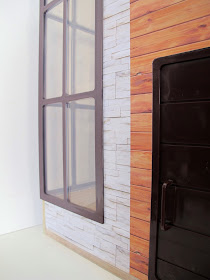 Front view of the modern Lori Loft to Love dolls' house, showing the front door and corner windows.