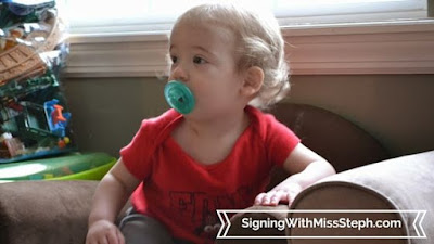One year old sitting in toddler sized chair with pacifier in mouth
