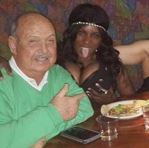Mean Gene Okerlund with his younger date, a busty black woman.