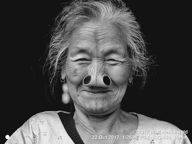 matt hahnewald photography; facing the world; character; face; tattoo; face tattoo; tribal tattoo; eyes; nose; nose plugs; lived-in face; wrinkles; facial expression; eye contact; consent; empathy; emotion; ethnic; traveling; tribal; adivasi; rural; village; traditional; cultural; hong; ziro; arunachal pradesh; northeast india; asian; indian; apatani; one person; female; adult; old; woman; picture; photo; face perception; physiognomy; educational; nikon d3100; nikkor af-s 50mm f/1.8g; prime lens; 50mm lens; nifty fifty; 4x3 aspect ratio; horizontal orientation; street; portrait; closeup; headshot; full-face view; outdoors; posing; authentic; unique; yaping hullo; yesso; shutterstock; smiling; black-and-white; monochrome; greyscale
