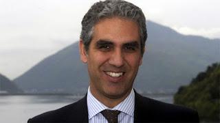 Una foto di Marcello Foa sorridente in giacca e cravatta in riva a un lago