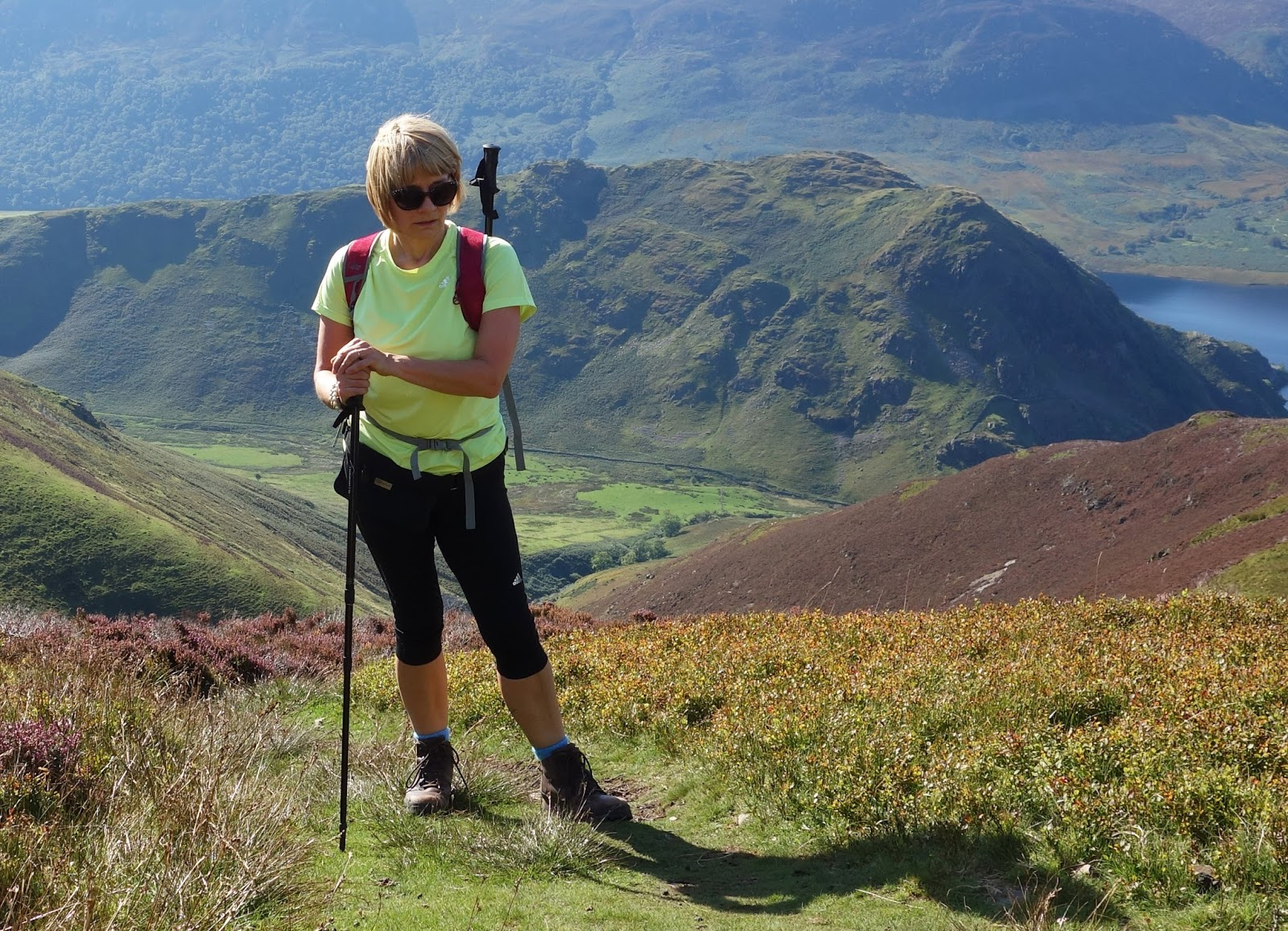Gail Hanlon from Is This Mutton? on a hill climb overlooking Buttermere Lake, wearing a yellow top and leggings from Adidas