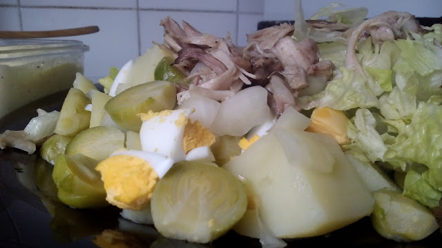 Plato de ensalada templada con patatas, pollo, coles de bruselas y lechuga