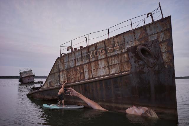 Un viejo barco encallado es e lienzo para la pintura de una bella mujer