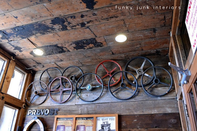 Vintage steering wheels hung from wood wall at Mission Springs Brewing Company, a junk-filled pub and restaurant.