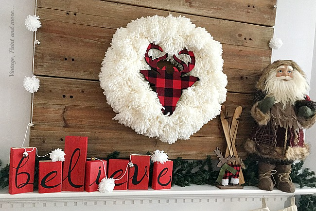 Vintage, Paint and more... a rustic farmhouse Christmas mantel made with a diy pom-pom garland, a diy believe sign and a diy yarn wreath with a buffalo plaid deer head