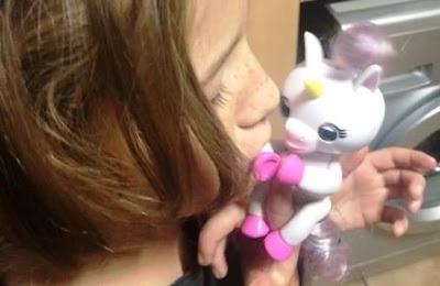 Girl kisses Fingerlings Baby Unicorn
