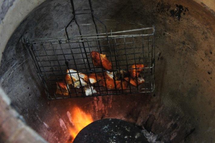 Cooking tandoori chicken in a tandoor oven