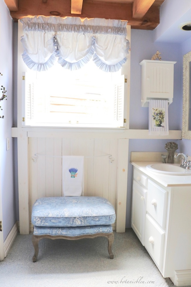 small white vanity area in master bathroom with French blue and white toile ottoman