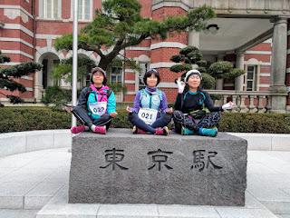 東京駅のモニュメントの台の上に3人座って瞑想のポーズ