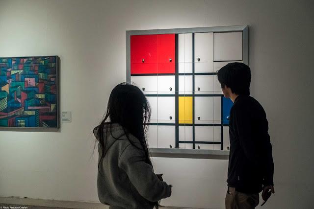 Dois jovens no Museu Oscar Niemeyer - MON olhando um quadro