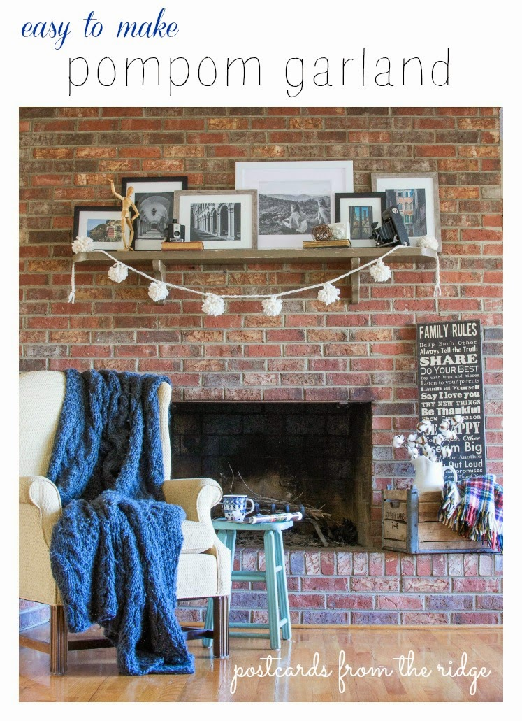 pom pom garland on brick fireplace