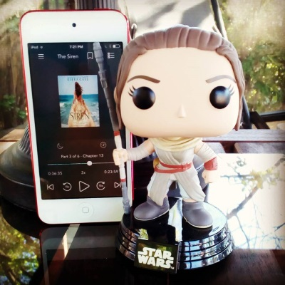 A Funko Pop bobblehead of Rey from Star Wars stands next to an iPod with The Siren's cover on it screen. The cover features a pale-skinned, long-haired brunette girl in a sandy yellow ball gown. She stands facing the ocean, her back to the viewer.