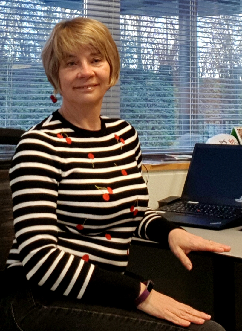 Image showing a woman at her desk wearing a black and white striped jumper decorated with cherries