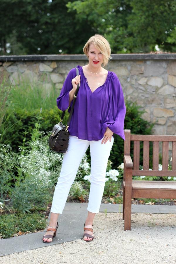 Lila Seidenbluse mit weißer Skinny-Jeans