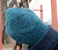 Someone wearing cabled mittens, with their hands wrapped around a lamp post.  The mittens have a cable pattern on the back of the mitten, with the cables enclosing double-moss stitch.