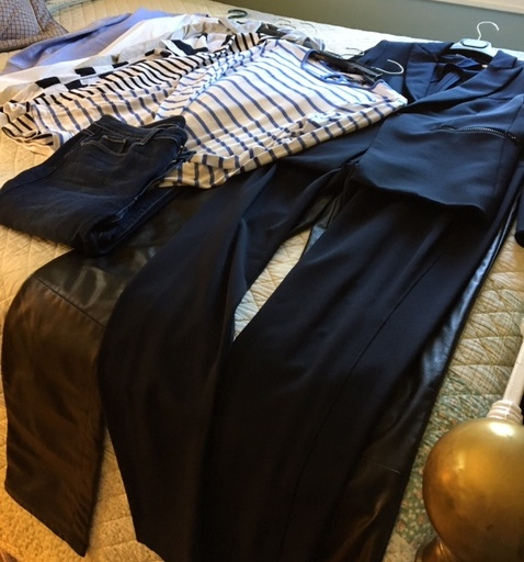 tee shirts, jeans and leather pants on a bed