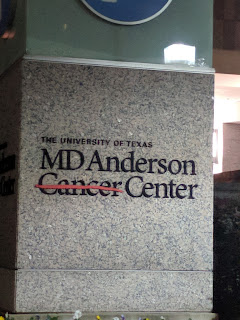 The MD Anderson Cancer Center Logo displayed on a granite waymarker. The word cancer is crossed out.