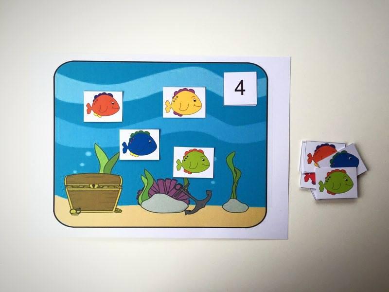 Zabawa, w której dziecko uczy się liczyć konkretne obiekty oraz poznaje cyfry.